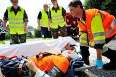 Männer packen an, um einen Verletzten zu bergen. (Bild: Donato Caspari)