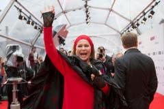 Die Schweizer Filmlegende Ursula Andress grüsst die Fans auf dem roten Teppich. (Bild: Keystone)