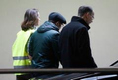 Ein Care-Team-Mitglied führt zwei Männer weg, die auf Passagiere des Unglücksflugs gewartet haben. (Bild: Keystone)