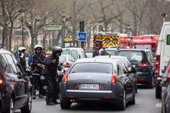 Polizisten riegeln eine Strasse nahe des Tatorts in Paris ab. (Bild: Keystone)