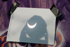 So war das Spektakel ungefährlich für die Augen: Die Sichel der Sonne wird von einem Fernrohr auf ein Blatt projiziert. (Bild: Keystone)