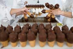 """Mitarbeiter von Gasparini tauchen Rahmglaces in flüssige Schokoladenmasse. Das """"Zolli-Cornet"""" wird in Münchenstein im Kanton Basel-Land produziert. (Bild: Keystone)"""