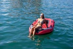Eine junge Frau geniesst den Sommer auf einem Schlauchboot auf dem Zürichsee. (Bild: WALTER BIERI (KEYSTONE))