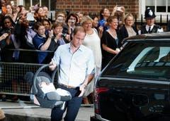 Da hat wohl jemand heimlich geübt: Prinz William spediert die Trage mit seinem Sohn gekonnt ins Auto. (Bild: Keystone)