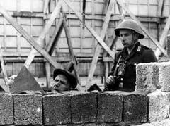 Unter der Bewachung eines DDR-Grenzpolizisten beseitigen Bauarbeiter am 26. Mai 1962 Sprengstoffschäden an der Berliner Mauer in der Bernauer Strasse/Ecke Schwedter Strasse. Eine Explosion kurz nach Mitternacht hatte ein zwei Meter breites Loch in die Mauer gerissen. (Bild: Keystone)