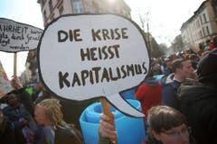 """""""Die Krise heisst Kapitalismus"""" steht auf dem Plakat einer Demonstrantin. (Bild: Keystone)"""