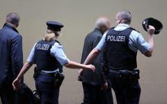 Einsatzkräfte führen zwei Angehörige von Absturzopfern in einen geschützten Bereich des Düsseldorfer Flughafens. (Bild: Keystone)