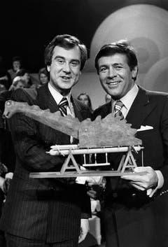 Im Fernseh-Quiz «Wer gwünnt?» vom 17. Dezember 1976 in Luzern versteigern Kurt Felix (links) und Mäni Weber das Teleboy-Seeungeheuer «Nessie». (Bild: Keystone)