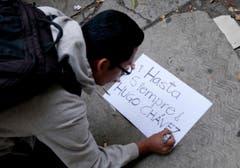 Ein Unterstützer Chávez' schreibt ein Schild. (Bild: Keystone)