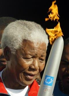 Nelson Mandela amtet als Träger einer Fackel mit dem Olympischen Feuer (2004). (Bild: Keystone)