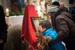 Bevor die Gläubigen in der Kirche ihren Platz einnehmen, küssen sie die Bilder der Ikonen und erbitten Gesundheit, Zufriedenheit und Glück. (Bild: Ralph Ribi)