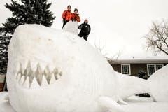 Freude am Schnee haben diese drei Brüder. Sie haben einen fast fünf Meter grossen Wal im Garten gebaut. (Bild: Keystone)
