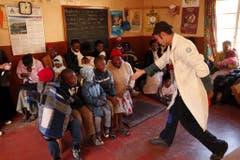 Der Clown Jamie Lachman (rechts)gibt am 10. Juli 2008 einem kranken Knaben in einer Klinik in Lesotho die Hand und versucht ihn zum Lachen zu bringen. (Bild: Keystone)