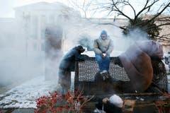 Obdachlose wärmen sich an einem Dampfabzug der Staatlichen Handelsbehörde in Washington. (Bild: Keystone)