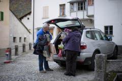 Zwei Dorfbewohner entladen ihr Hab und Gut. (Bild: KEYSTONE/Gian Ehrenzeller)