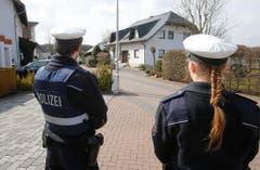 Zwei Polizeiangehörige beim Haus, wo der Co-Pilot der Germanwings-Maschine lebte. Er soll den Airbus extra zum Absturz gebracht haben. (Bild: Keystone)
