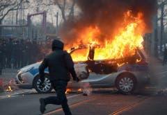 Ein Polizeiauto steht in Flammen. (Bild: Keystone)
