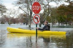 Hochwasser nach Supersturm Sandy, soweit das Auge reicht - und trotzdem scheint sich dieser Mann an die Signalisation zu halten. (Bild: Keystone)