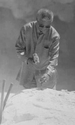 Nelson Mandela demonstriert, wie er während seiner Gefangenschaft auf Robben Island Kalkstein abbauen musste (1995). (Bild: Keystone)