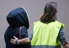 Eine Angehörige wird am Flughafen Düsseldorf weggebracht. (Bild: Keystone)