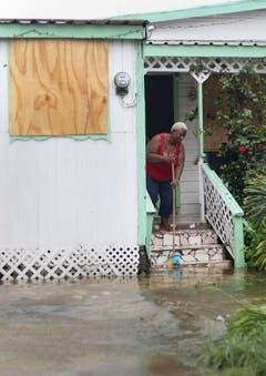 Ein Frau wischt Wasser aus dem Haus nachdem der Tropensturm Irma St.John's, Antigua and Barbuda passiert hat. (Bild: Keystone)