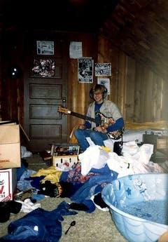 Mit der Gitarre im Dachboden: Ein undatiertes Foto zeigt den jungen Kurt Cobain in seinem Elternhaus in Aberdeen. Mit 14 erhielt er seine erste Gitarre von seinem Onkel Chuck. (Bild: Keystone)