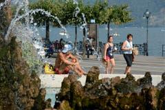 Menschen verschaffen sich Kühlung beim Brunnen fontana di Piazza Manzoni in Lugano. (Bild: Keystone)