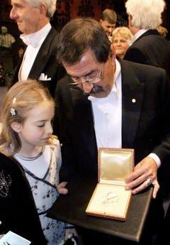 Der stolze Grossvater: Günter Grass zeigt seiner Enkelin Rosanne den Literaturnobelpreis, den er 1999 gewonnen hat. (Bild: Keystone)