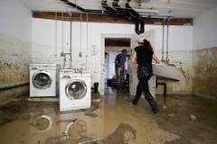 Eine Frau räumt ihre Waschküche aus, die unter Wasser steht. (Bild: Keystone)