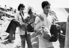 Die vom Gas erblindeten Kinder aus der indischen Stadt Bhopal werden von Helfern zum Spital gebracht. (Bild: Keystone)