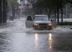 Ein Pickup fährt durch die geflutete Brickell Avenue in Miami, Florida. (Bild: Keystone)
