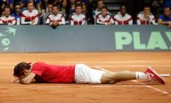 Erschöpft liegt Roger Federer nach dem Spiel am Boden. (Bild: Keystone)