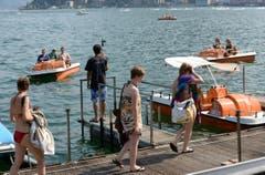 Menschen erfrischen sich an diesem heissen Sommertag mit einem Bad im See in Lugano. (Bild: Keystone)