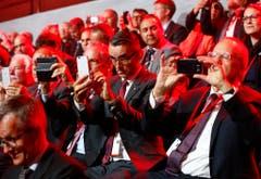 Die Gäste der Eröffnungszeremonie zücken ihr Handy um ein Erinnerungsbild zu schiessen. (Bild: Keystone)