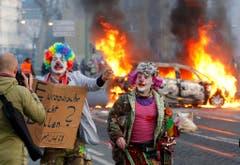 Demonstranten in Clown-Kostüms protestieren gegen den Kapitalismus. (Bild: Keystone)