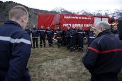 Feuerwehrleute und Sanitäter besprechen ihren Einsatz. (Bild: Keystone)