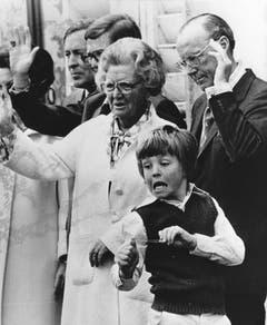 Am 2. Mai 1978 zielt der zehnjährige Prinz Johan Friso mit einem elastischen Band auf die Kameramänner während seine Grossmutter Königin Juliana und Grossvater Prinz Bernhard am 69. Geburtstag der Königin der Menge zuwinken. (Bild: Keystone)