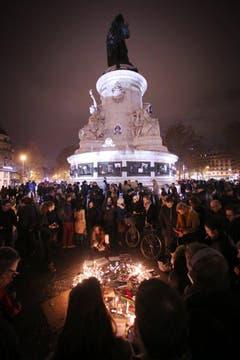 Die Menschen zünden auf den Place de la Republique in Paris Kerzen an. (Bild: Keystone)
