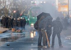 Maskierte Demonstranten schützen sich mit einem Schirm vor den Wasserkanonen der Polizei. (Bild: Keystone)