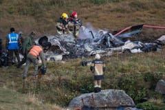 Feuerwehrleute löschen Flammen in den Trümmern des Helikopters. (Bild: Keystone)