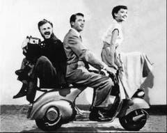 """Das Sujet dieser Spritztour aus dem Jahr 1953 zieren bis heute in Italien Kalender und Postkarten: Audrey Hepburn und Gregory Peck (2.v.r.) brausen im Erfolgsstreifen """"Roman Holiday"""" auf einer Vespa durch Rom. (Bild: STR (AP NY))"""