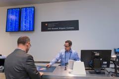 Ein Mitarbeiter des Zolls informiert einen Passagier. (Bild: Ralph Ribi)