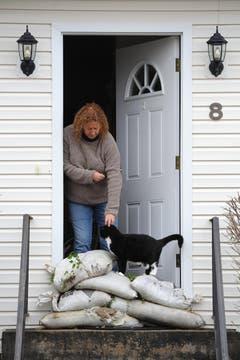Paula Bacco mit ihrer Katze Phoebe. Den Eingang zum Haus hat Bacco mit Sandsäcken verbarrikadiert. (Bild: Keystone)