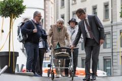 Ruth Roduner wird von ihrem Sohn Dieter (links) und Hanspeter Krüsi, Chef Kommunikation der Kantonspolizei St.Gallen, zur Feier geleitet. (Bild: Keystone)