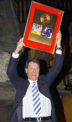 """Udo Jürgens erhält am 28. Mai 2004 für sein Album """"Es lebe das Laster"""" eine goldene Schallplatte und freut sich darüber. (Bild: Keystone)"""