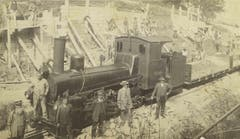 Eine schöne fotografische Studie mit Bauarbeitern (hinten), Zugspersonal (vorne an der Lokomotive) und zwei deutlich besser gekleideten Männern rechts vor der Lok. Die beiden könnten Aufsichtsfunktionen über die Baustelle im Hintergrund haben. Beim Bauprojekt handelt es sich um eine Verbreiterung der Teufener Strasse bei der Hochwacht. Das undatierte Bild könnte von 1913 stammen, als hier für die städtische Trambahn Platz geschaffen wurde. (Bild: Stadtarchiv der Ortsbürgergemeinde St.Gallen)