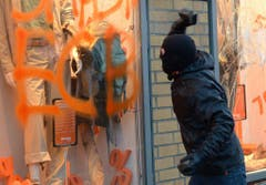 Ein Demonstrant wirft einen Stein in ein verspraytes Schaufenster in Frankfurt. (Bild: Keystone)
