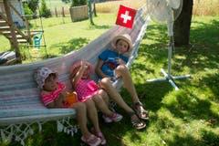 Diese drei Kinder relaxen in der Hängematte und lassen von einem Ventilator die Luft erfrischen. (Bild: Keystone)
