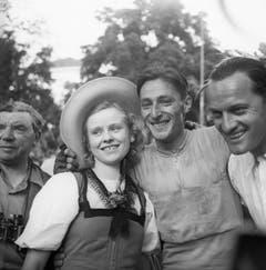 Ferdy Küber, der Sieger der zweiten Hälfte der 3. Etappe der 12. Tour de Suisse, am 14. Juni 1948 von La-Chaux-de-Fonds nach Thun, posiert am Ziel mit einem Mädchen in Tracht. (Bild: Keystone)