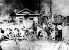 Japanische Opfer warten wenige Stunden nach dem Atombombenabwurf im Süden Hiroshimas auf erste Hilfe. (Bild: Keystone)